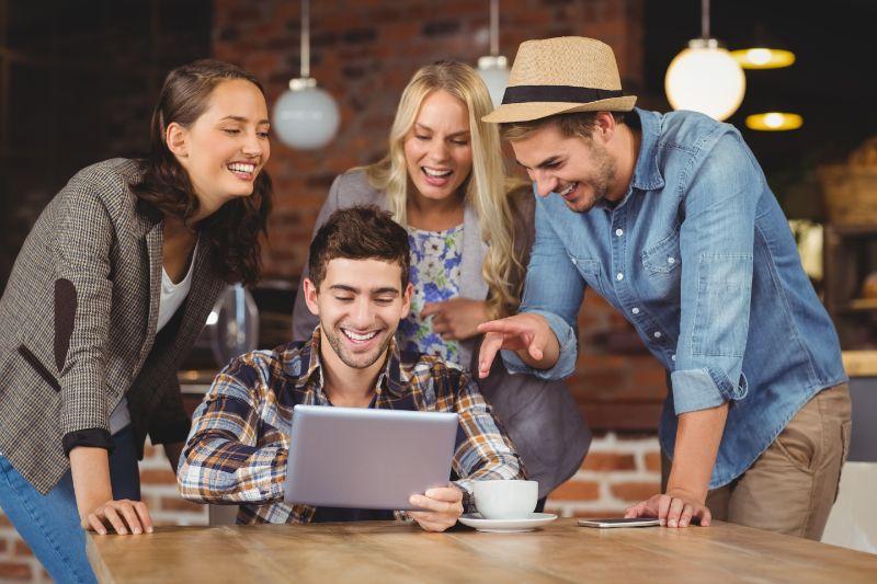 Lachende-Freunde-die-Tablet-Computer-betrachten