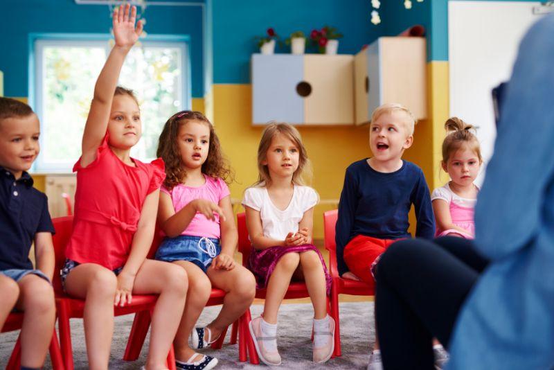 Madchen-das-ihre-Hand-hebt-um-Frage-im-Klassenzimmer-zu-stellen-oder-antworten
