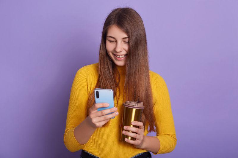 Madchen-halt-ein-Handy-und-einen-Drink