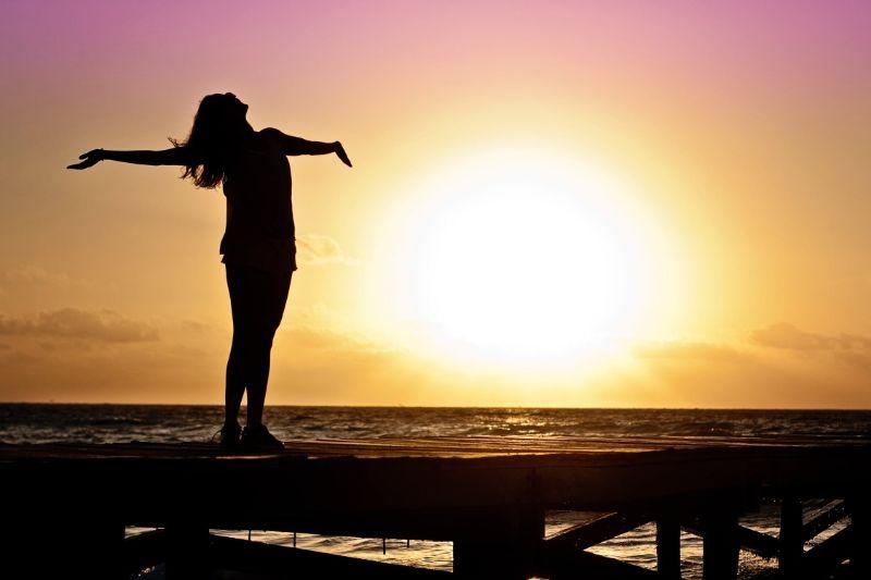 Madchen-mit-ausgebreiteten-Armen-die-den-Sonnenuntergang-umarmen