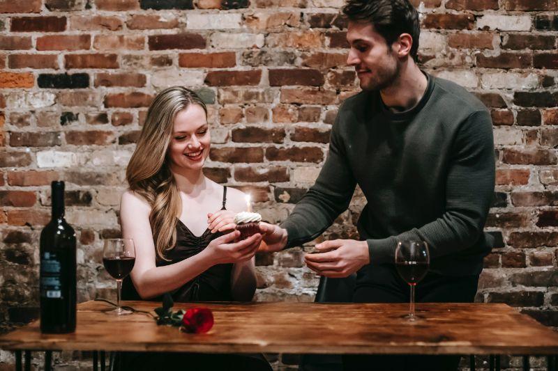 Mann gibt einem Mädchen einen Cupcake