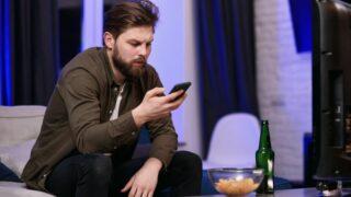 Mann mit Bart hält ein Handy und trinkt Bier