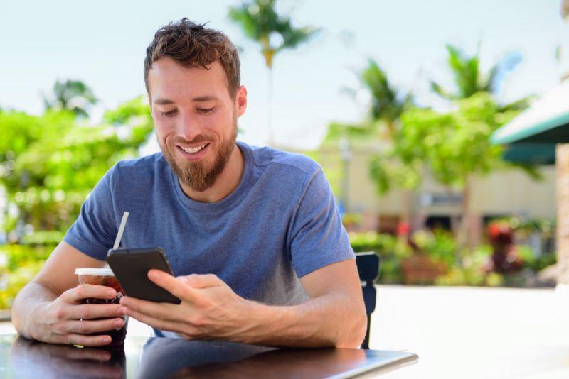 Mann-mit-Smartphone-der-kalten-Kaffee-trinkt