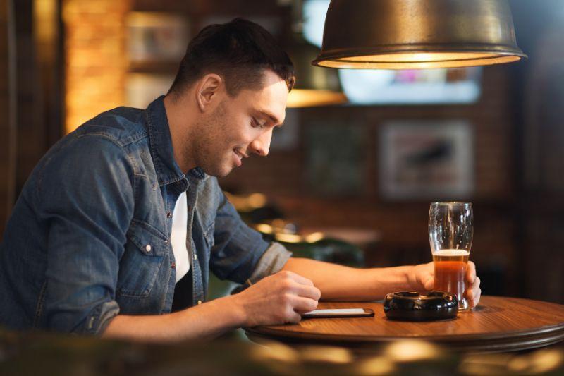 Mann-mit-Smartphone-und-Bier-SMS-an-der-Bar