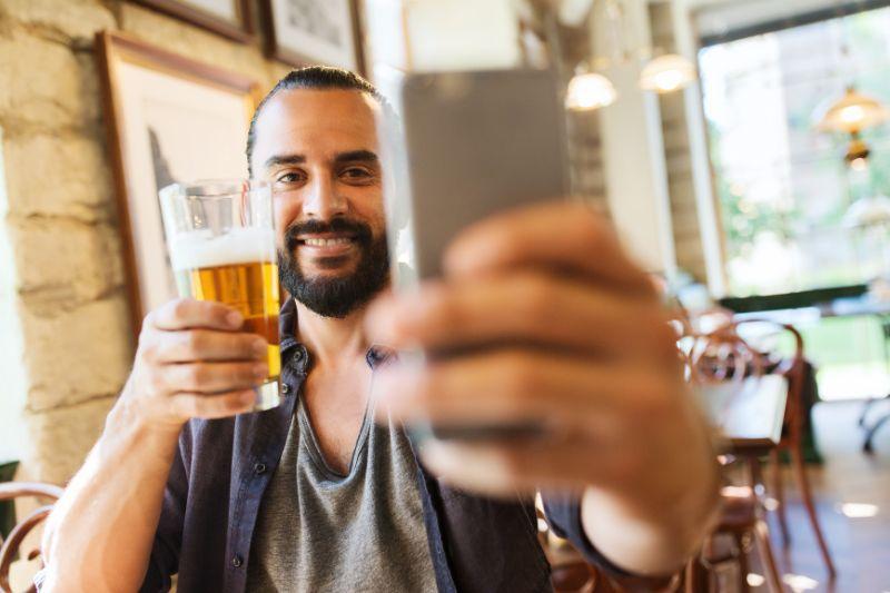 Mann-mit-dem-Smartphone-das-Bier-trinkt