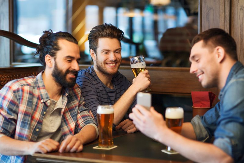 Mannliche-Freunde-mit-Smartphone-das-Bier-an-der-Bar-trinkt