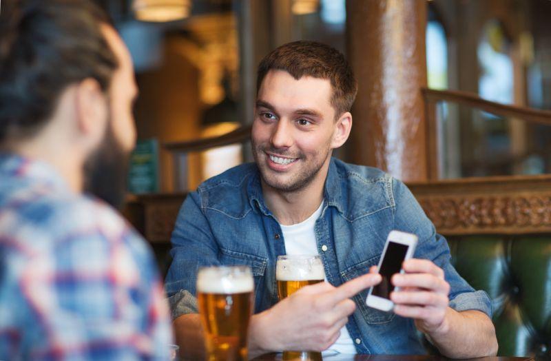 Mannliche-Freunde-mit-Smartphone-die-Bier-an-der-Bar-trinkt