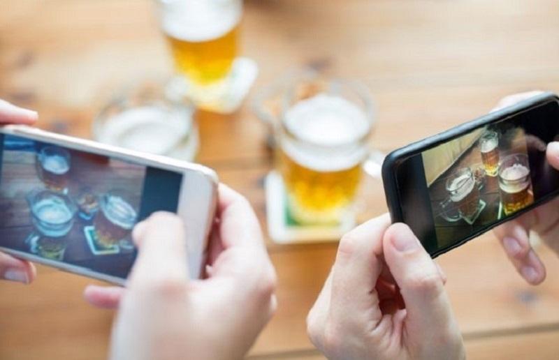 Nahaufnahme-der-Hande-mit-dem-Smartphone-das-Bier-darstellt-1