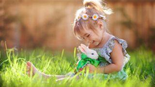 Nettes kleines Mädchen mit einem Häschen hat ein Ostern am grünen Gras