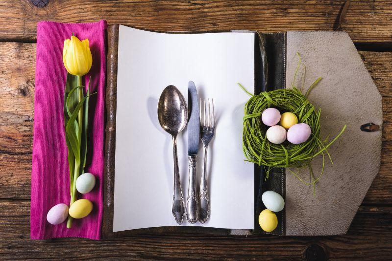 Ostermenu-auf-einem-Holztisch-mit-Eiern-und-frischen-Blumen-dekoriert