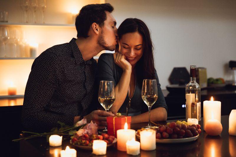 Schones-leidenschaftliches-Paar-das-ein-romantisches-Abendessen-bei-Kerzenlicht-zu-Hause-hat-und-kusst