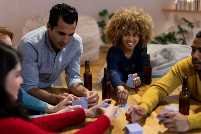 Tausendjahrige-erwachsene-Freunde-die-zu-Hause-zusammen-sind-Karten-spielen-Spiel-trinken