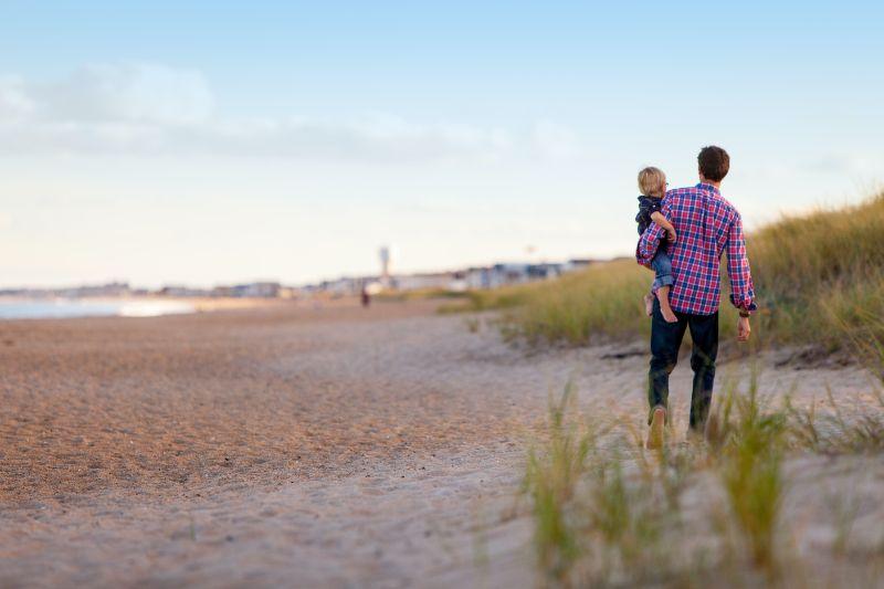 Vater-halt-Kind-und-geht-am-Strand-spazieren