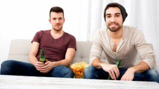 Zwei Freunde, die zu Hause fernsehen und trinken