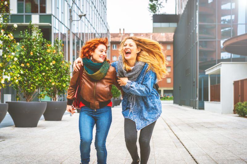 Zwei junge Frauen, die im Freien in der Stadt spazieren gehen, die Spaß haben