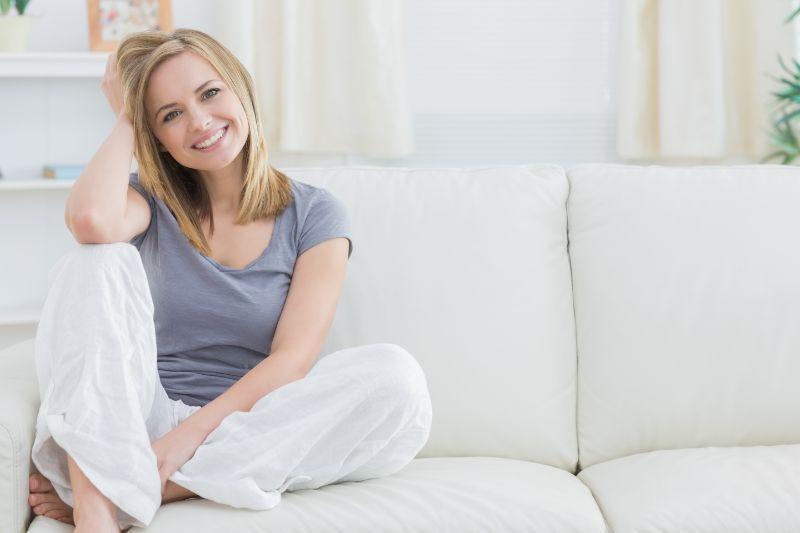 gluckliche-Frau-zu-Hause-sitzen-auf-ihrem-Sofa