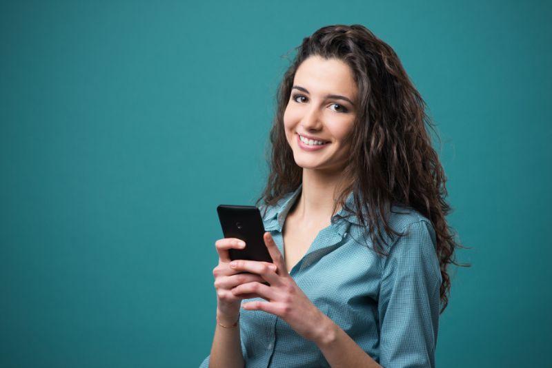 schone-Frau-mit-dem-lockigen-Haar-das-ein-Handy-halt