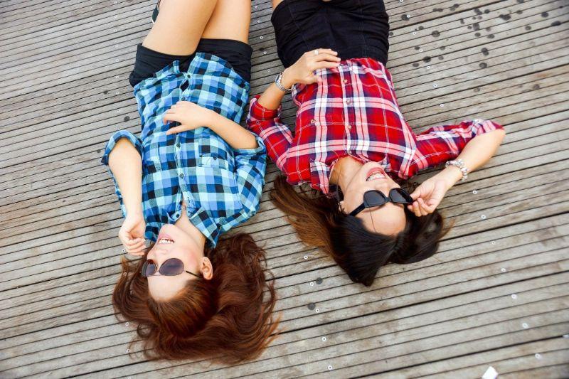 zwei-Freunde-die-auf-Holzboden-liegen