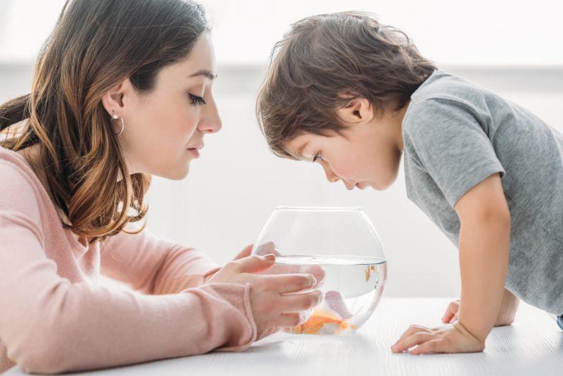Attraktive-Frau-mit-entzuckendem-Sohn-der-in-Fischschussel-zu-Hause-schaut