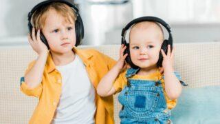 Entzückende Brüder, die zu Hause Musik in Kopfhörern hören