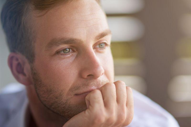 Erfreut-uber-mein-Leben.-Portrat-eines-zufriedenen-gutaussehenden-Mannes-der-zur-Seite-schaut-und-seine-Hand-am-Kinn-halt-wahrend-er-uber-sein-Leben-nachdenkt-min