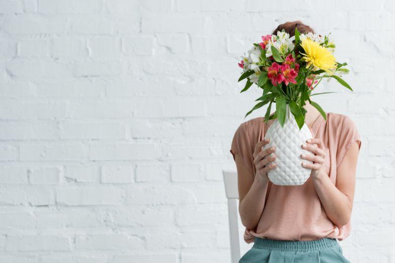 Frau-die-Gesicht-mit-Blumen-in-der-weisen-Vase-vor-der-weisen-Backsteinmauer-bedeckt