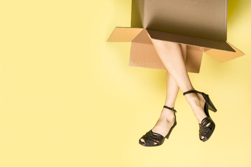 Frauenbeine-kommen-aus-einem-Karton