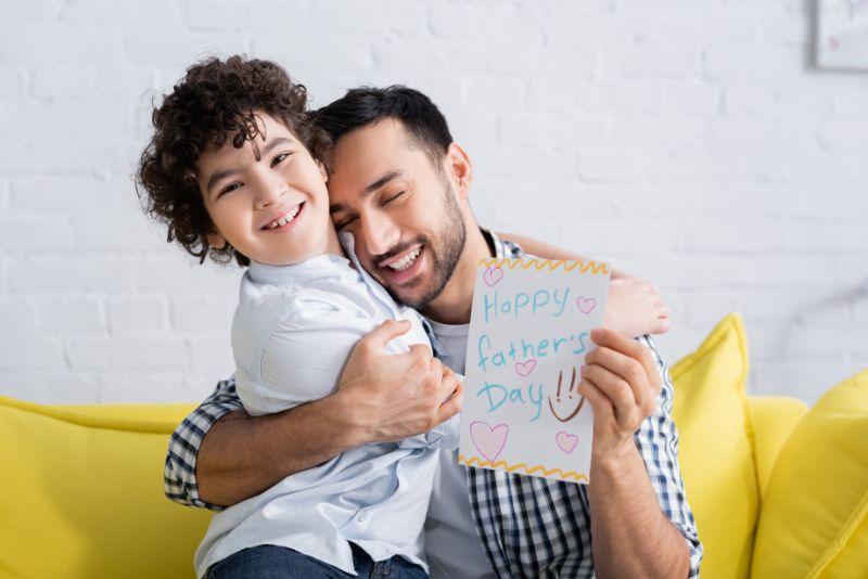 Freudiger-Mann-der-glucklichen-Sohn-umarmt-wahrend-gluckliche-Vatertagskarte-halt