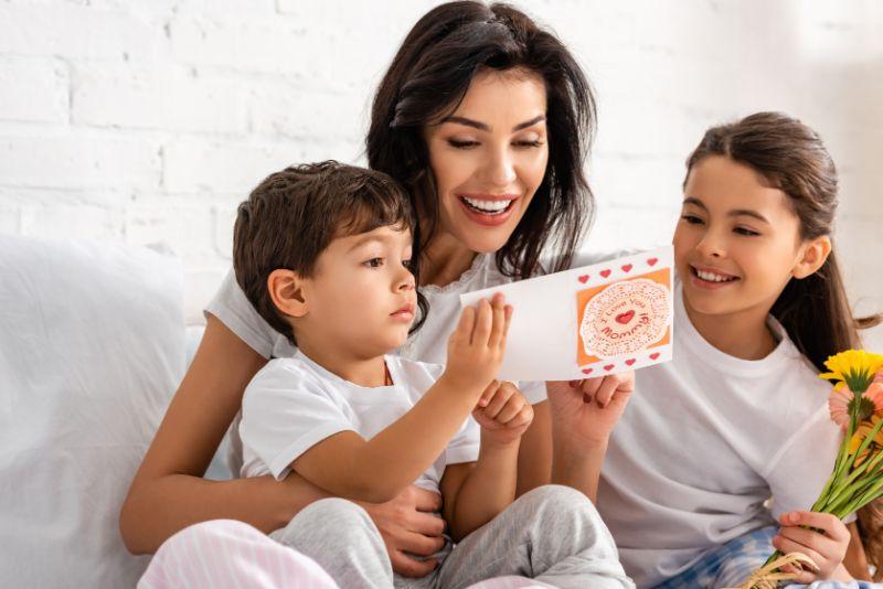 Gluckliche-Frau-die-Muttertagskarte-liest-wahrend-sie-im-Bett-mit-entzuckenden-Kindern-sitzt