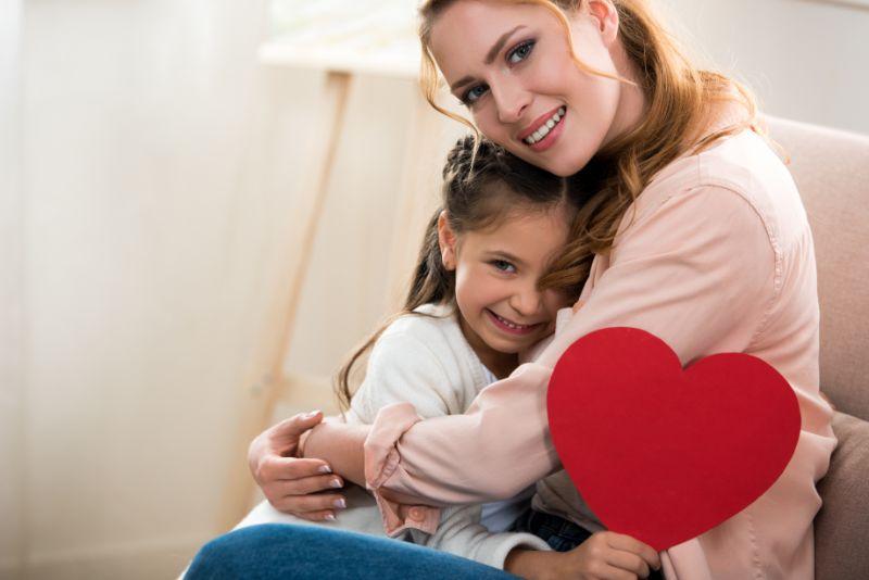 Gluckliche-Mutter-und-Tochter-mit-rotem-Herzsymbol-das-Kamera-umarmt-und-lachelt