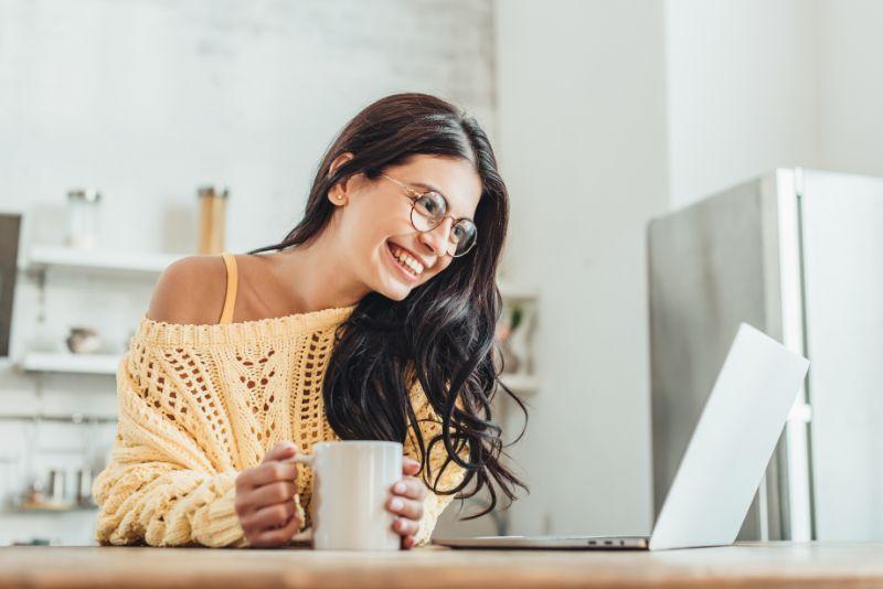 Junge-lachende-Freiberuflerin-die-am-holzernen-Tisch-mit-Laptop-und-Kaffeetasse-in-der-Kuche-zu-Hause-sitzt