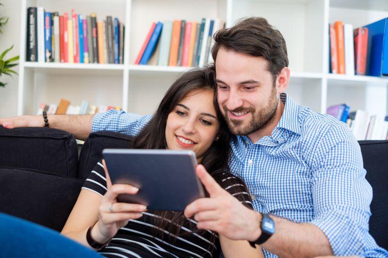 Junges Paar, das Internetmedieninhalt auf digitalem Tablett betrachtet