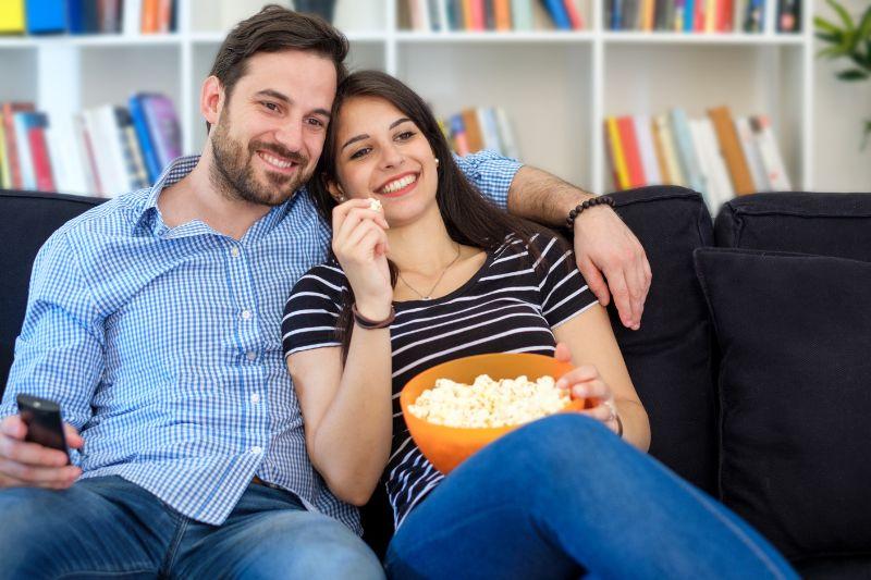 Junges-Paar-das-zu-Hause-fernsieht-und-Spas-hat