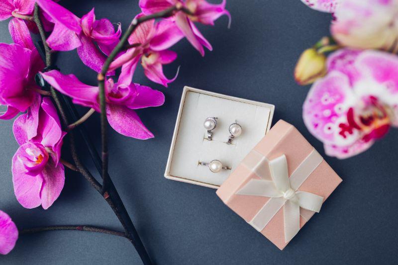 Klassischer-stilvoller-weiblicher-Schmuck.-Silberring-und-Ohrringe-mit-Perlen-in-Geschenkbox-mit-rosa-Orchideenblumen-auf-grauem-Hintergrund.