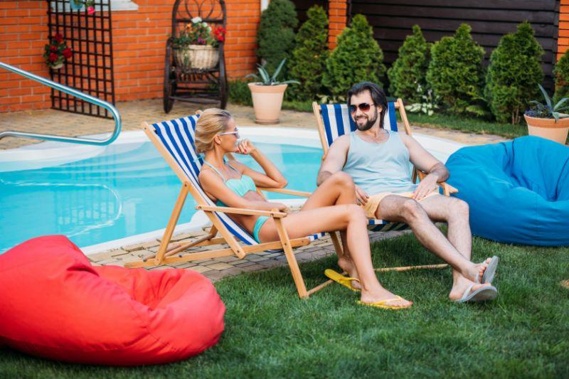 Lachelndes-Paar-auf-Liegestuhlen-die-Zeit-in-der-Nahe-des-Schwimmbades-am-Hinterhof-am-Sommertag-verbringen