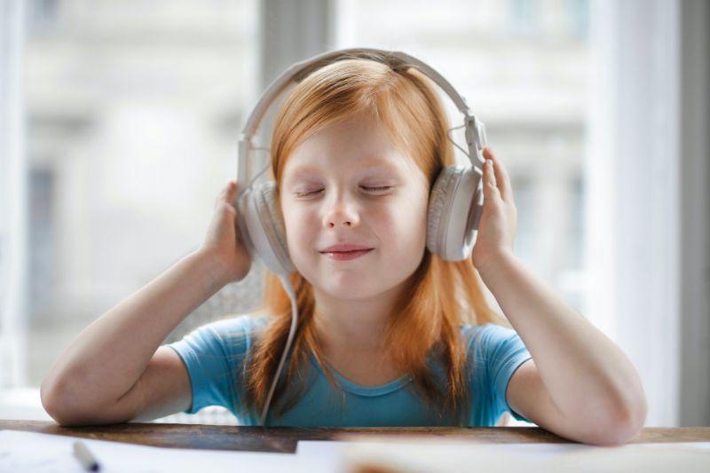 Madchen-mit-orangefarbenen-Haaren-hort-mit-Kopfhorern-eine-Geschichte