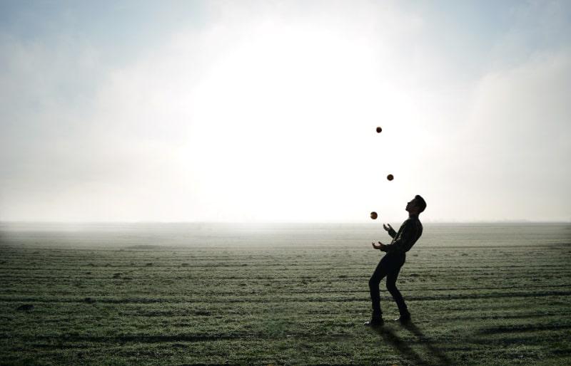 Mann-jonglierte-mit-3-Ballen-auf-einem-Feld
