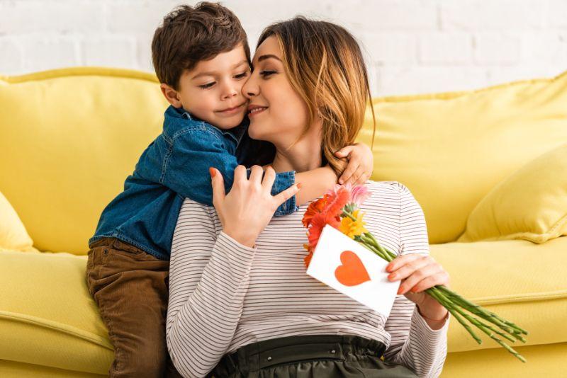 Netter Junge, der Mutter umarmt, die Blumen und Muttertagskarte mit Herzsymbol hält