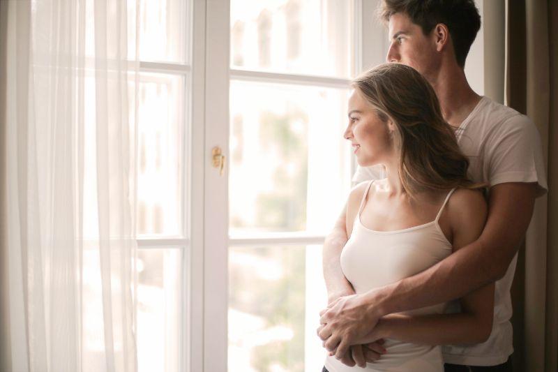 Paar-umarmt-und-schaut-durch-das-Fenster