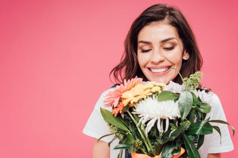 Schone-Frau-mit-geschlossenen-Augen-die-Blumenstraus-halten
