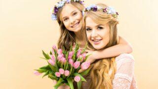 Schöne Frau und entzückende Tochter, die Blumen hält