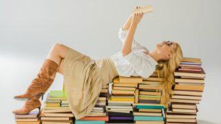 Schöne blonde Frau in den Gläsern, die auf Stapel Bücher lesen und legen