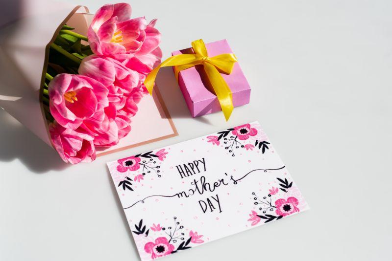 Sonnenlicht-auf-rosa-Tulpen-nahe-Geschenkbox-und-Gruskarte-mit-glucklich-Muttertagsbeschriftung