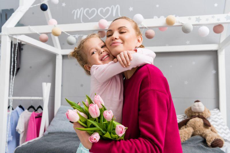 Tochter-prasentiert-Tulpenstraus-fur-Mutter-am-Muttertag