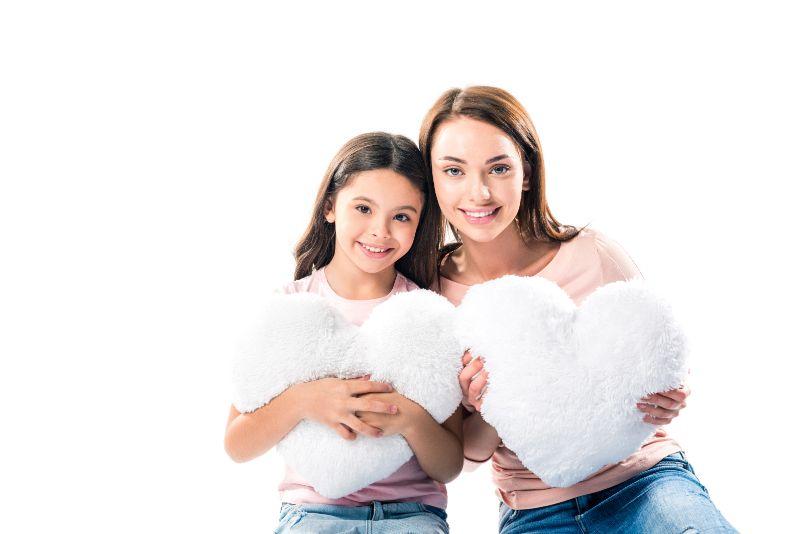 Tochter-und-Mutter-mit-herzformigen-Kissen