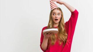 Überraschtes Mädchen, das Partykappe berührt und Geburtstagstorte hält
