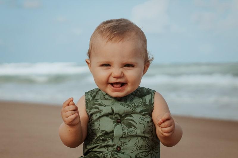 baby-junge-auf-dem-strand-das-lacht