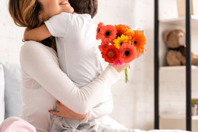 gluckliche-Mutter-die-Sohn-umarmt-wahrend-Blumen-am-Muttertag-halt