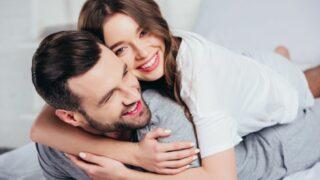 junges liebendes Paar, das im Bett umarmt und lächelt