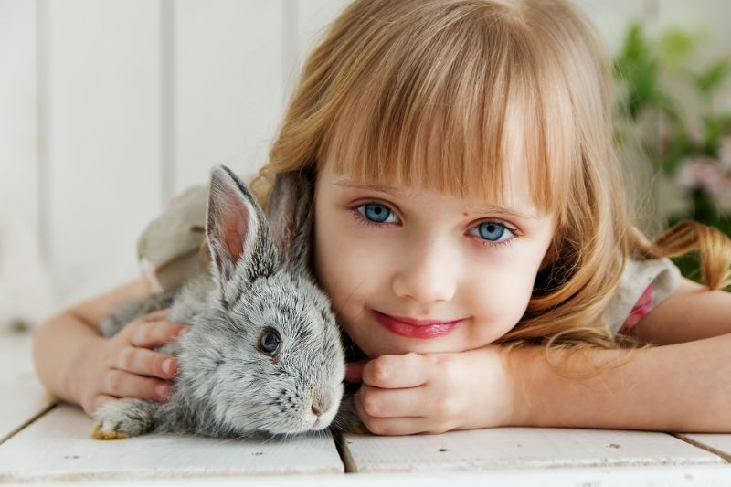 schones-blondes-Madchen-mit-blauen-Augen-die-ein-Kaninchen-halten
